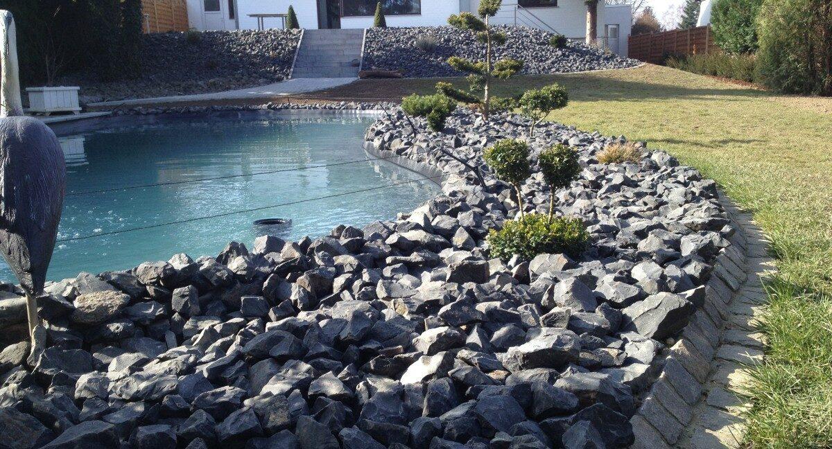 Teichanlage mit Natursteinumrandung und Bepflanzung